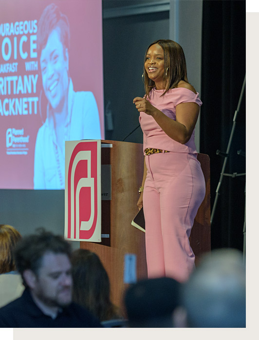 African American woman in pink clothes stands on stage beside a podium and screen.