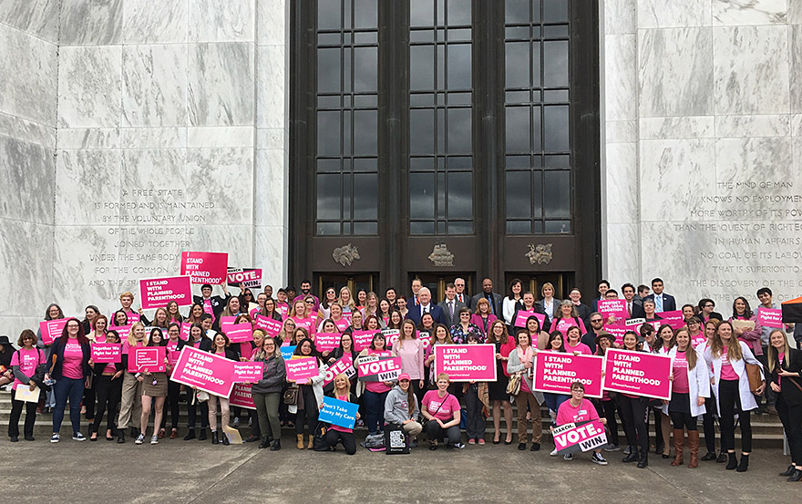 Large crowd of Planned Parenthood supporters sit and stand outside in front a building with Planned Parenthood signs.