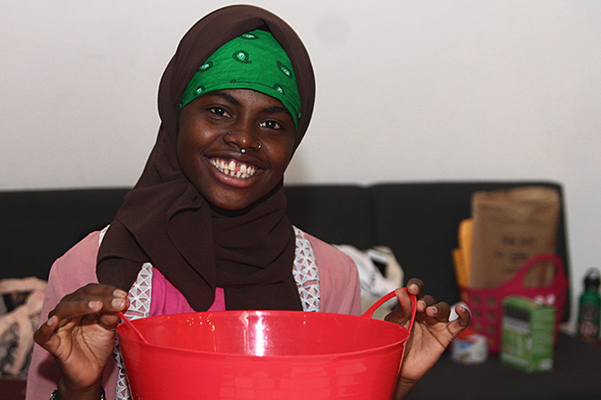 Young African American woman in green and brown head coverings smiles and holds up a red bucket.